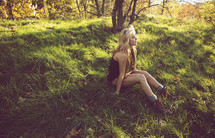 Female sitting in grassy field
