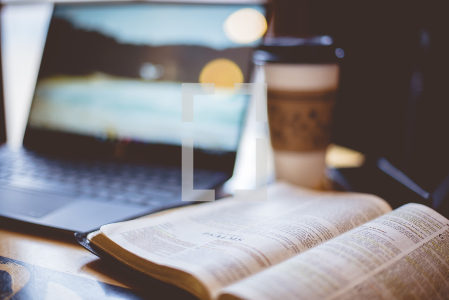 laptop computer, coffee cup, and opened Bible on a table