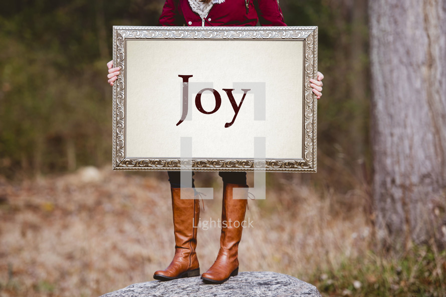 a woman holding a sign the reads joy