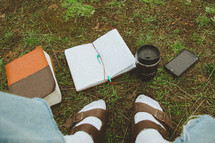 feet in socks and sandals near a Bible, notebook, and coffee cup