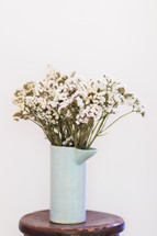 white flowers in a vase on a stool