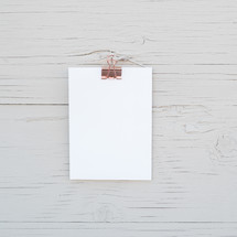 clip holding white paper on weathered wood board