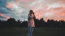 a woman taking a picture at sunset