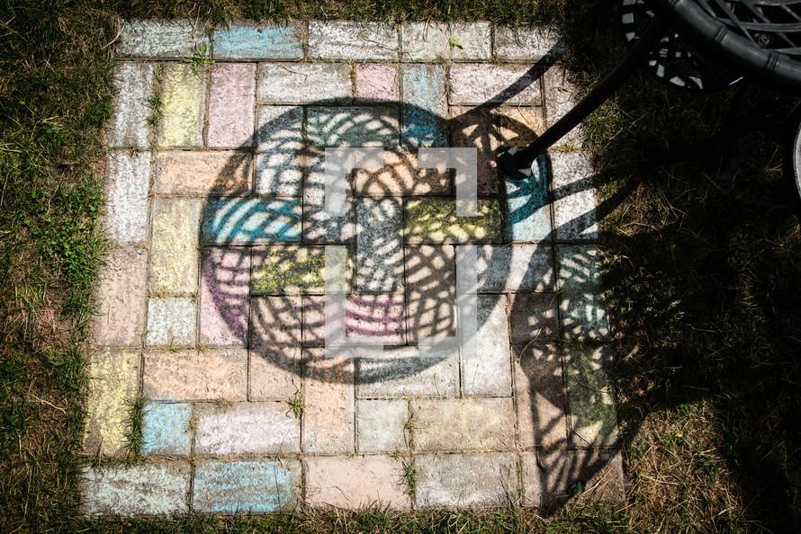 shadow on a patio covered in sidewalk chalk