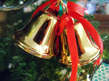 A set of Brass colored Christmas Bell Tree Ornaments adorned with red ribbons lighting up a  Christmas tree.