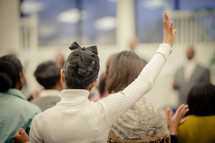 woman raising her hand in praise at a worship service