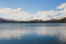 Clouds over snow-covered mountains surrounding a lake.