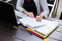 a woman at a desk looking at a laptop and writing in a notebook