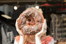 a woman holding up a giant donut
