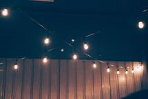 string of light bulbs strung from a ceiling