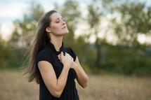 Woman praying in field