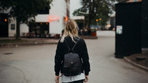 a young woman walking towards an outdoor restaurant