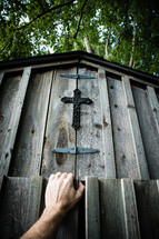 Opening the door to a wooden barn with a cross