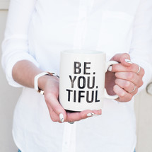 woman holding a mug with the words Be. You. Tiful.