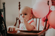 an infant in a high chair eating cake