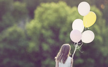 a girl walking with balloons