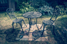 iron table and chairs on a patio outdoors