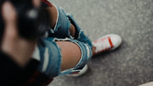 young woman in torn jeans and sneakers
