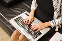 a woman sitting on a couch typing on a laptop