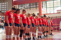 praying volleyball team holding hands