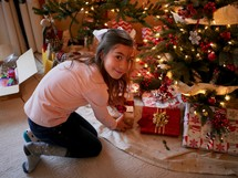 a girl looking at gifts under a Christmas tree