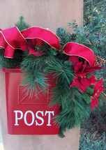 A red postal box mail box with the words POST is decorated with green branches, red flowers and red ribbons to celebrate Christmas and bring some Christmas cheer.