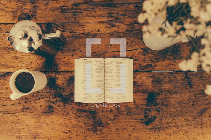 An open Bible and a cup of coffee on a rustic wooden surface.