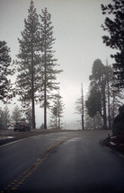 car parked on the side of a mountain road on a foggy morning