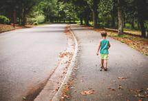 a little boy walking down a neighborhood sidewalk