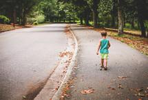 a little boy walking down a neighborhood sidewalk