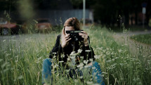 a young woman in tall grass holding a camera