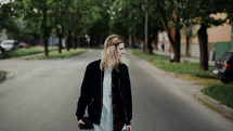 a young woman walking down a neighborhood street