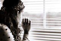 teen girl looking out window blinds
