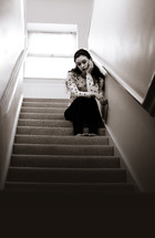 a sad teen girl sitting in a stairway