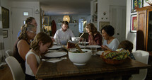 A family praying around a dinner table