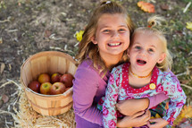 sisters with a basket of apples