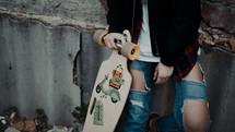 a teen girl holding a skateboard