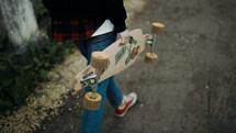 a teen girl carrying a skateboard
