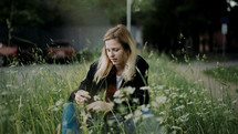 a young woman sitting in tall grass outdoors