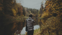 a man taking a picture of a pond in fall
