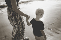 a mother and son walking on a beach holding hands