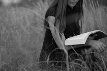 Woman reading Bible outdoors in an open field