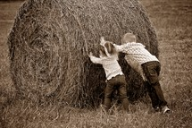 Children pushing a bail of hay