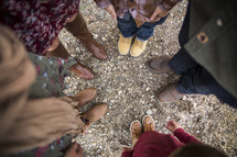 looking down at feet of a family standing in a circle