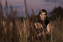 a woman in a field behind the blades of wheat grass