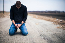 man kneeling on a road praying