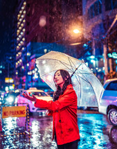 a woman standing in the rain holding an umbrella