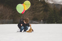 boy child walking in the snow carrying a balloon and teddy bear