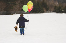 boy child walking in snow holding a teddy bear and balloons