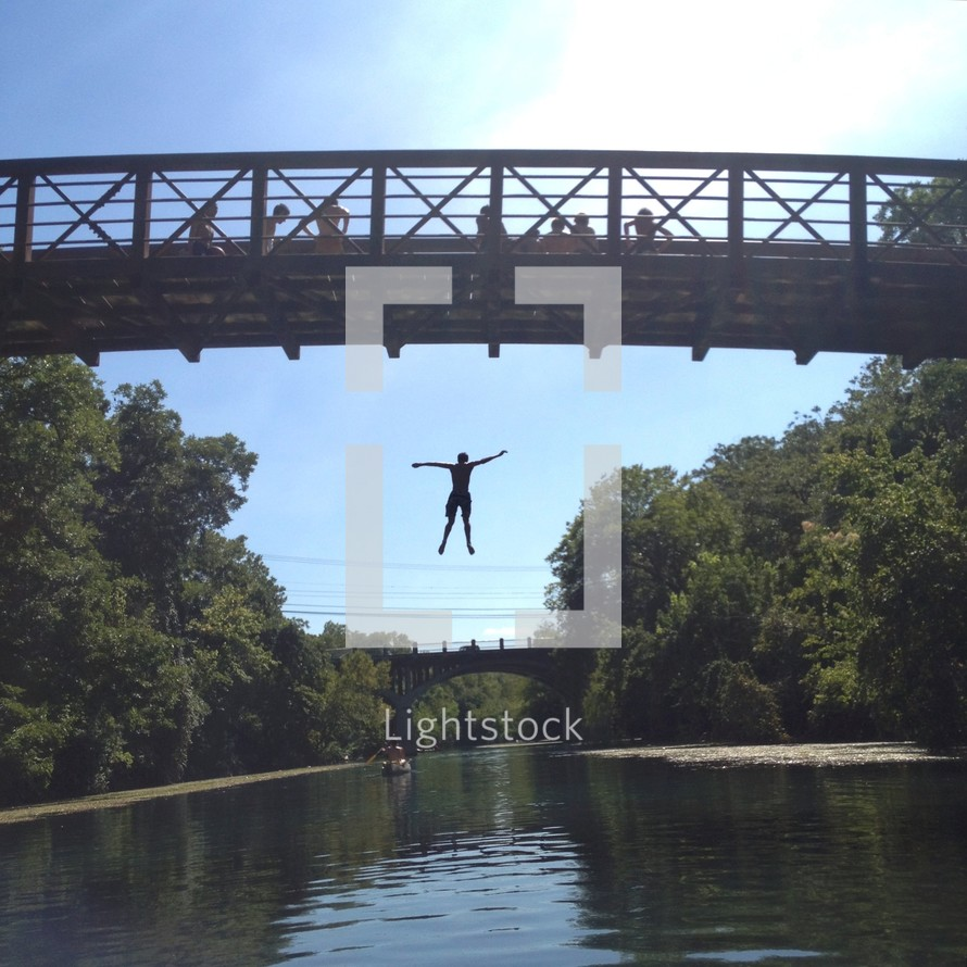 Man jumping from bridge into river